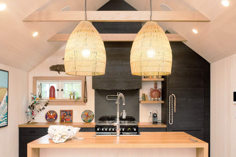 Armarios de madera de color negro manchados y lámparas colgantes tejidas en una cocina