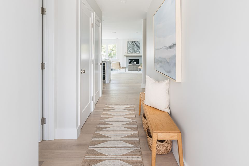 Hallway with wooden bench and white pillow on top with decorative rug and painting on wall
