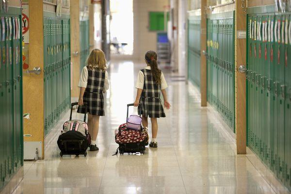 Second grade girls roll backpacks in school.