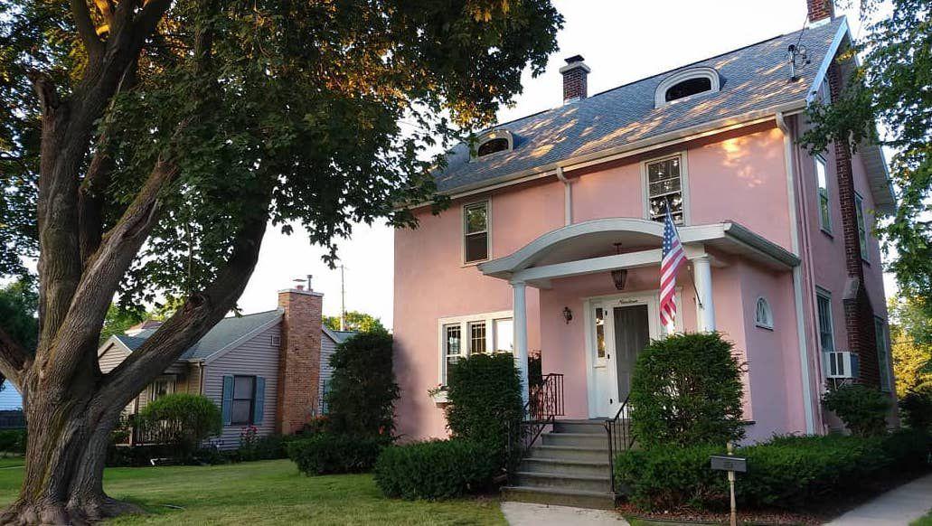 Casa de estuco rosa claro con detalles en blanco