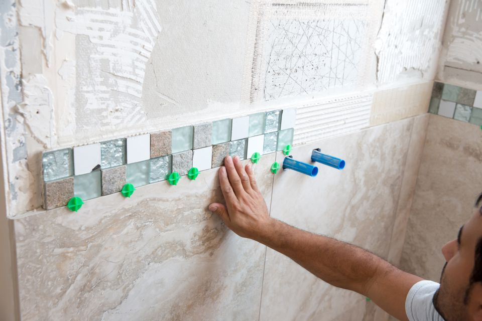A workman tiling a shower