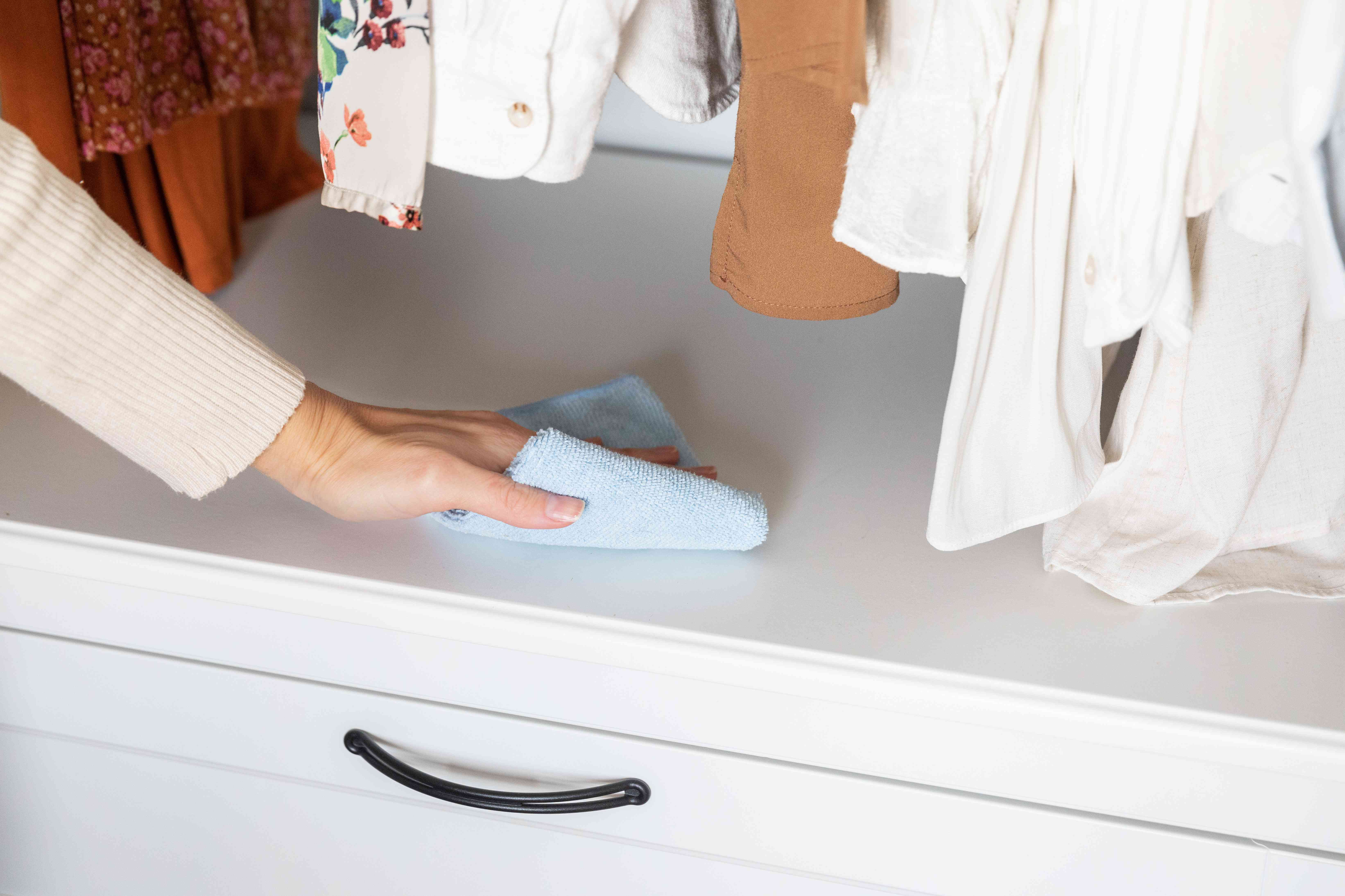 Wiping down closet cabinet with cloth to prevent insects eating clothes