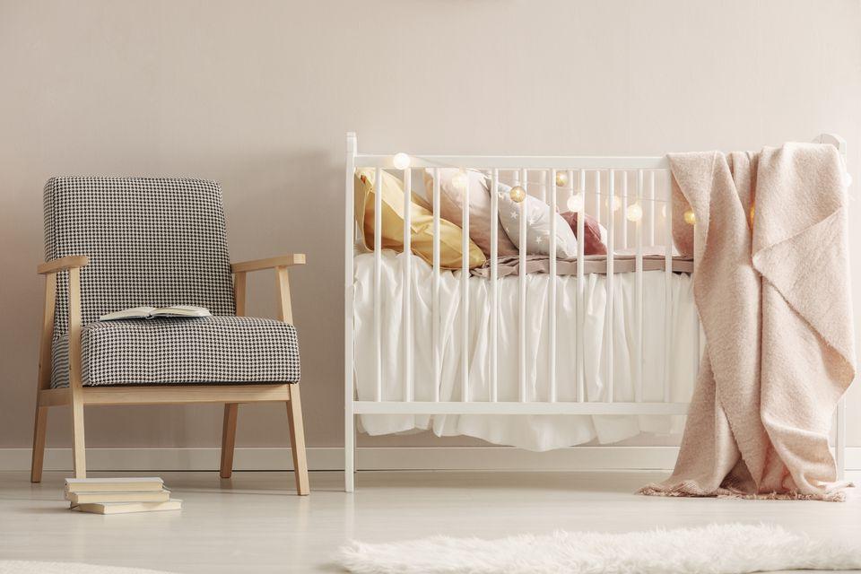 Open book on retro armchair next to white wooden crib with pastel bedding