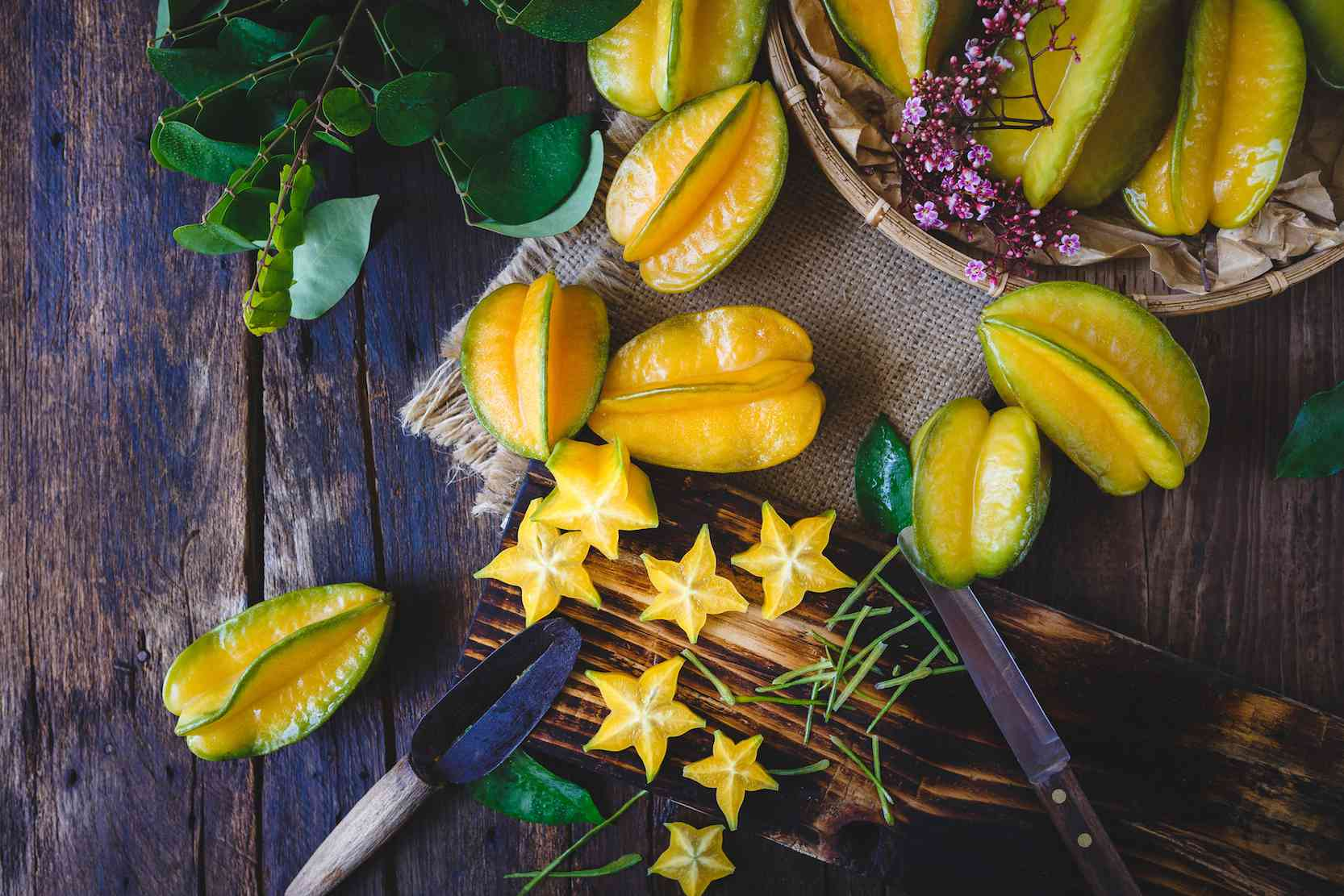 Starfruit sliced on plate with whole starfruits and blossoming branch with purple flowers