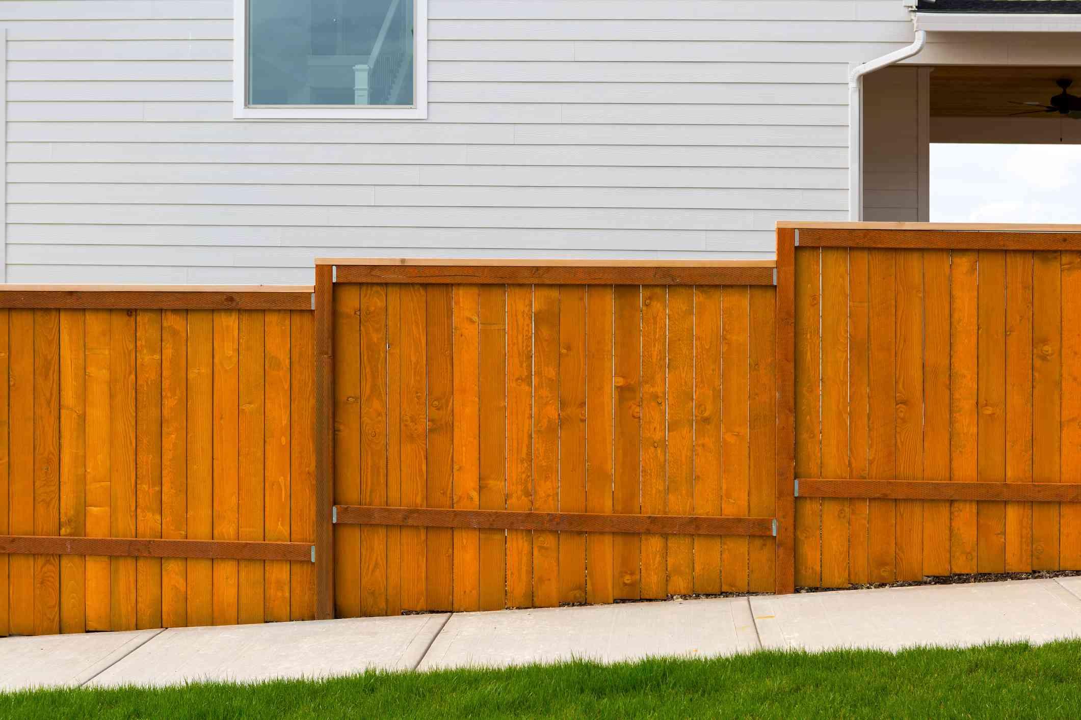 Construcción de cerca de madera de cedro teñida de rojo en el nuevo patio trasero