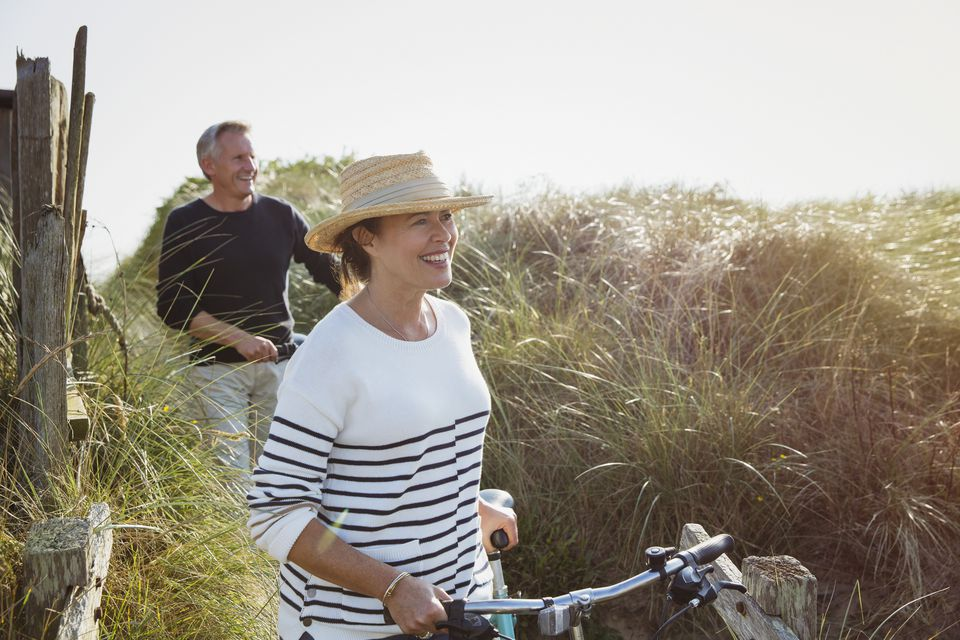 Mature couple walking bicycles along sunny beach grass