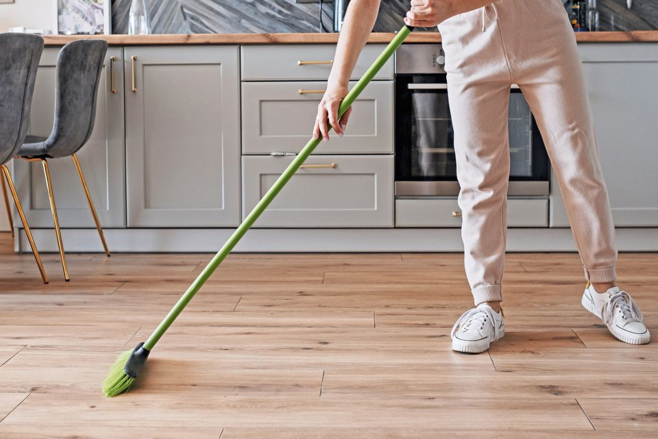 Wooden floors being swept with a green broom in kitchen with gray cabinets