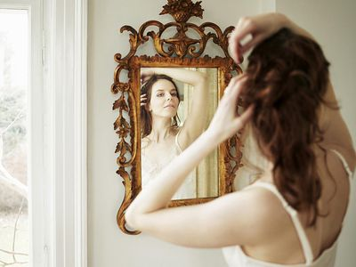Woman looking in mirror, fixing her hair (over the shoulder view)