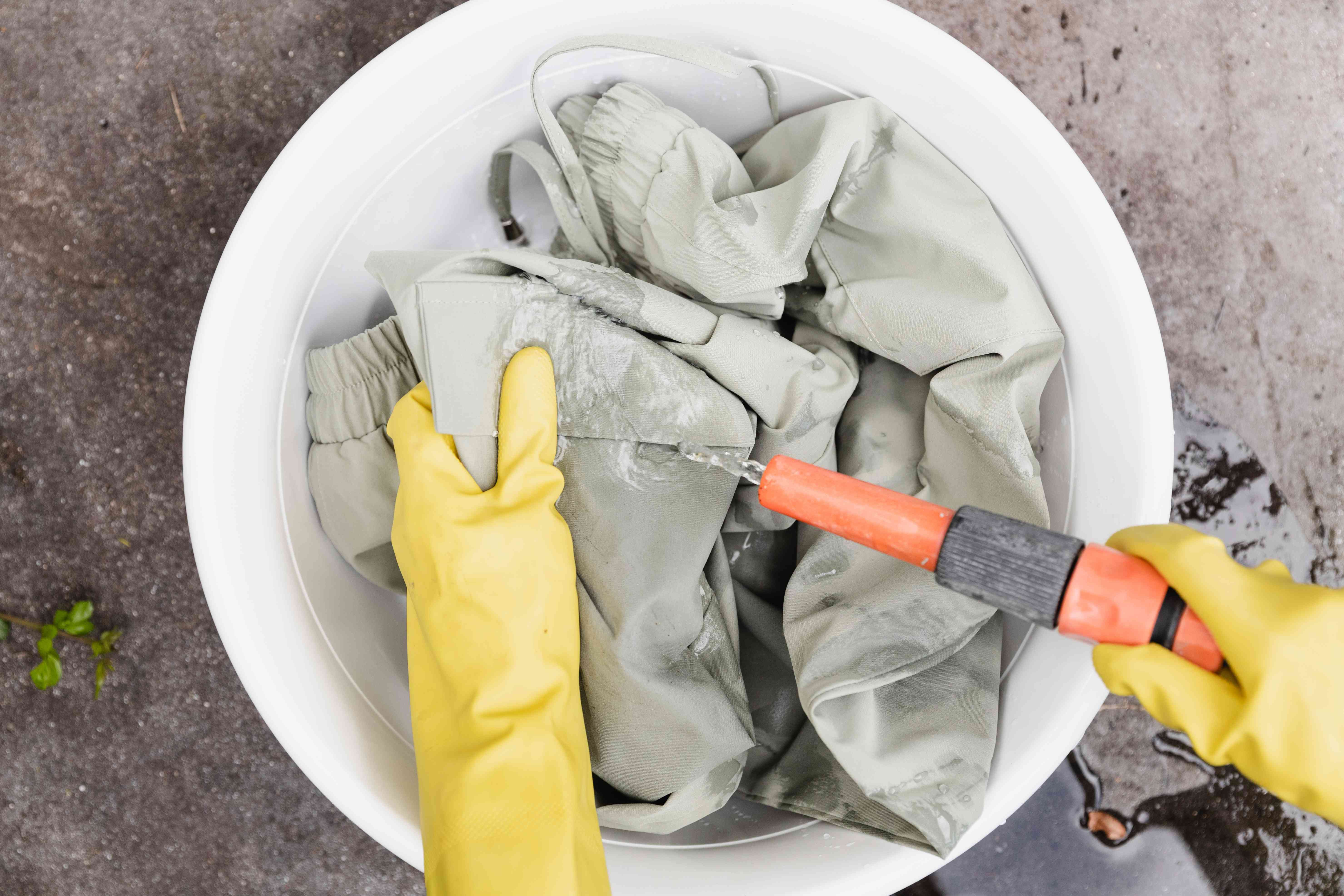 Chemical odors on grey pants being rinsed from orange hose with yellow gloves in white bucket