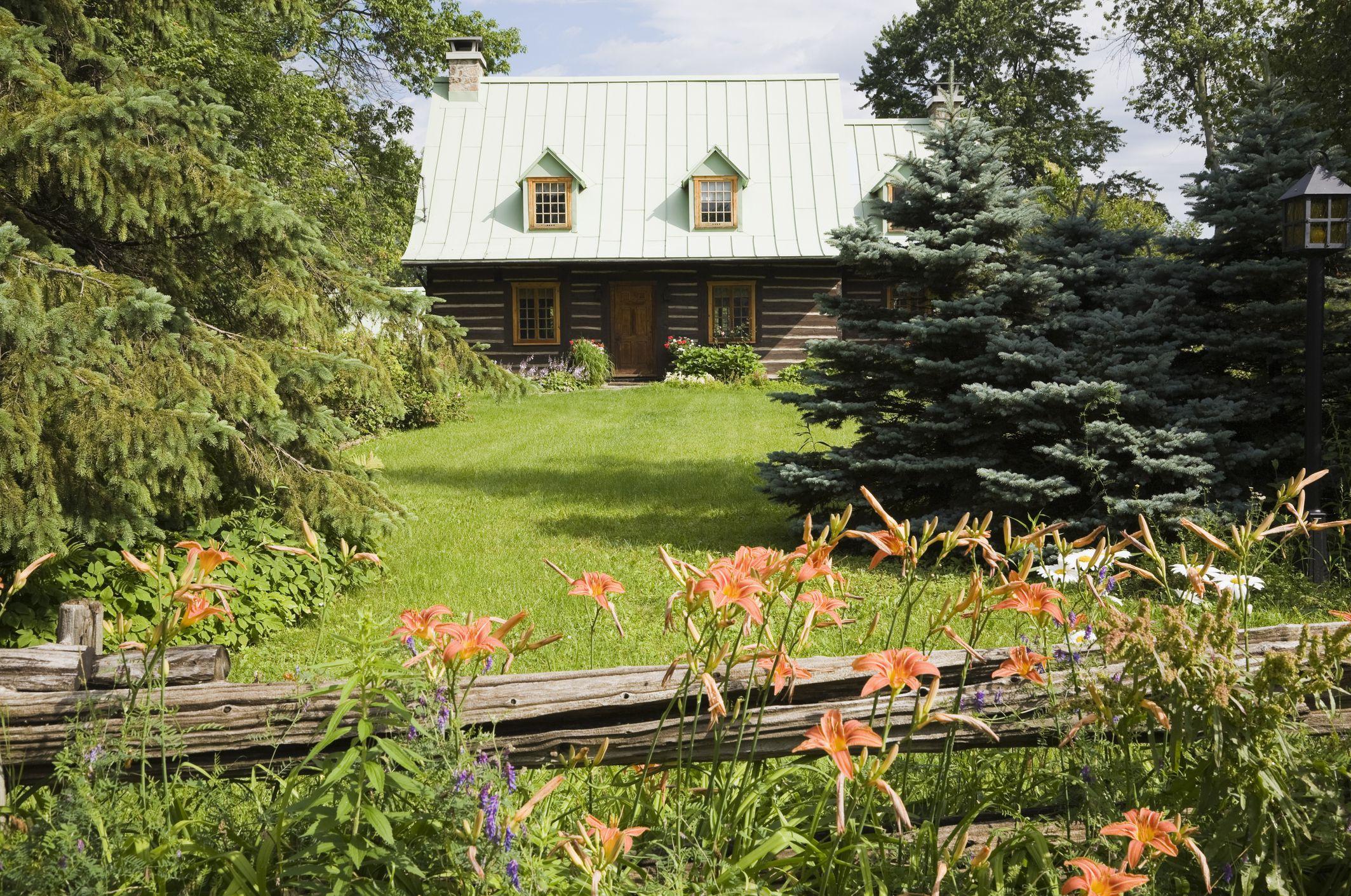 Casa rústica, con cerca rústica y plantaciones en primer plano