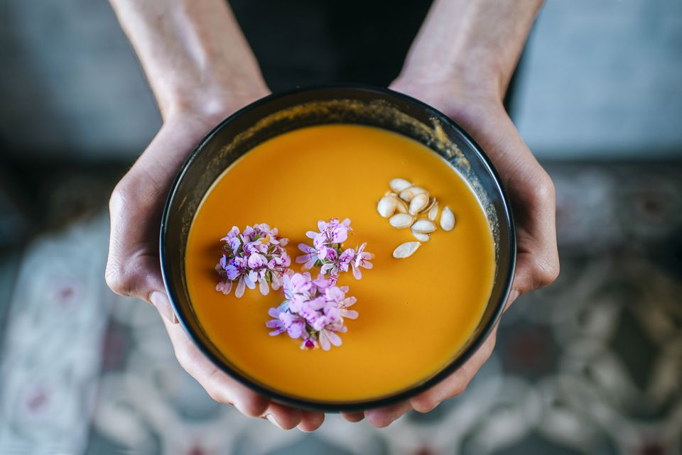 Hands holding creamed pumpkin soup garnished with edible flowers, close-up
