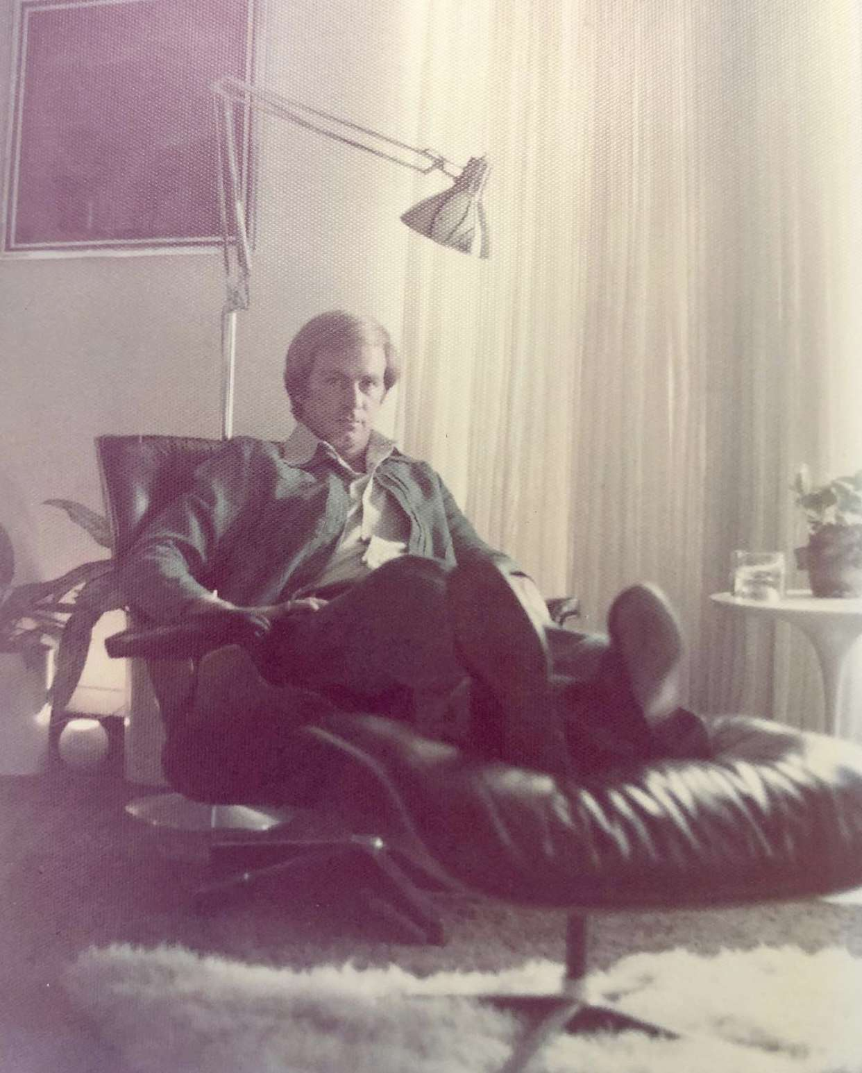 Kristen Nix's father poses in an authentic Eames lounge chair
