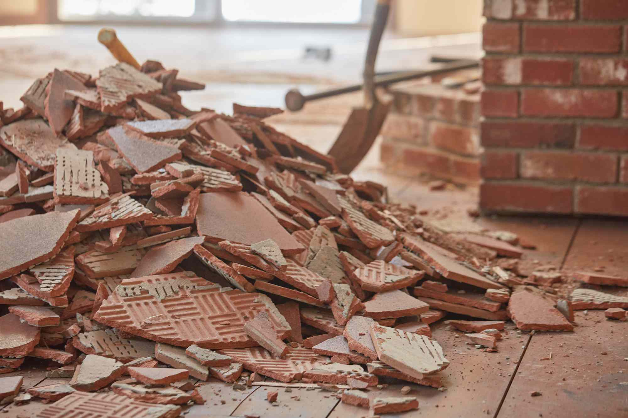 Pile of broken brown ceramic tile next to brick fireplace to be cleaned up