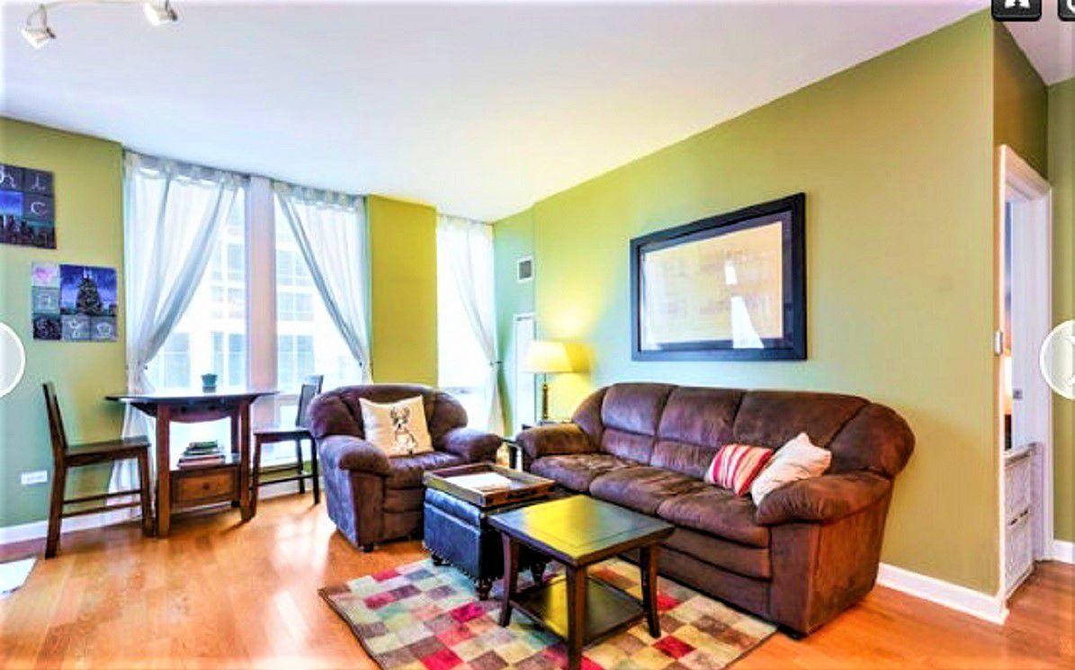 Sala de estar con paredes verdes y sofá anticuado . y silla antes del cambio de imagen