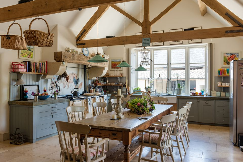 Vintage farmhouse table in rustic kitchen with green pendant lights from Holloways of Ludlow, aga, and beamed ceiling