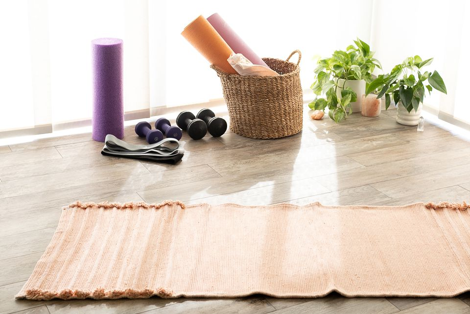 Home gym with orange mat on wooden surface with purple roller, basket of yoga mats and weights next to houseplants
