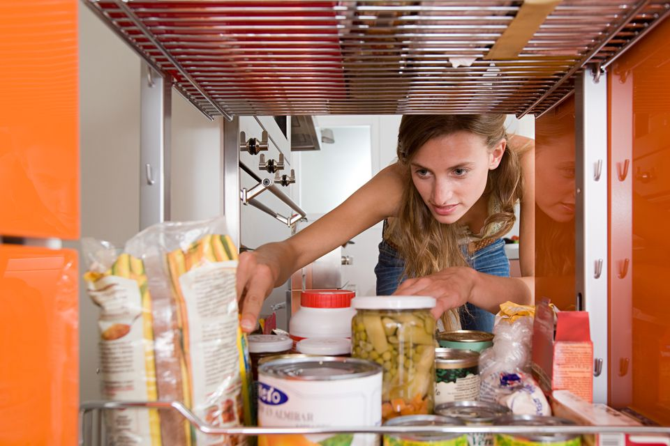 A woman reaching in cabinet for a packet of food