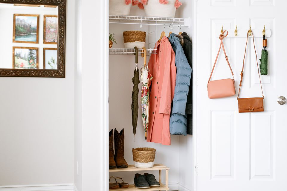 Coat closet organized with bag hooks, wire shelves and shoe bench