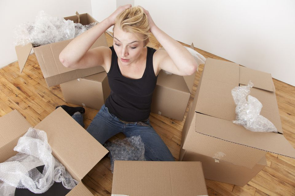 A woman, stressed out, surrounded by boxes