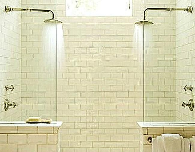 a double shower with white subway tile