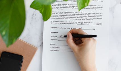 Apartment guarantor form signed by hand underneath houseplant