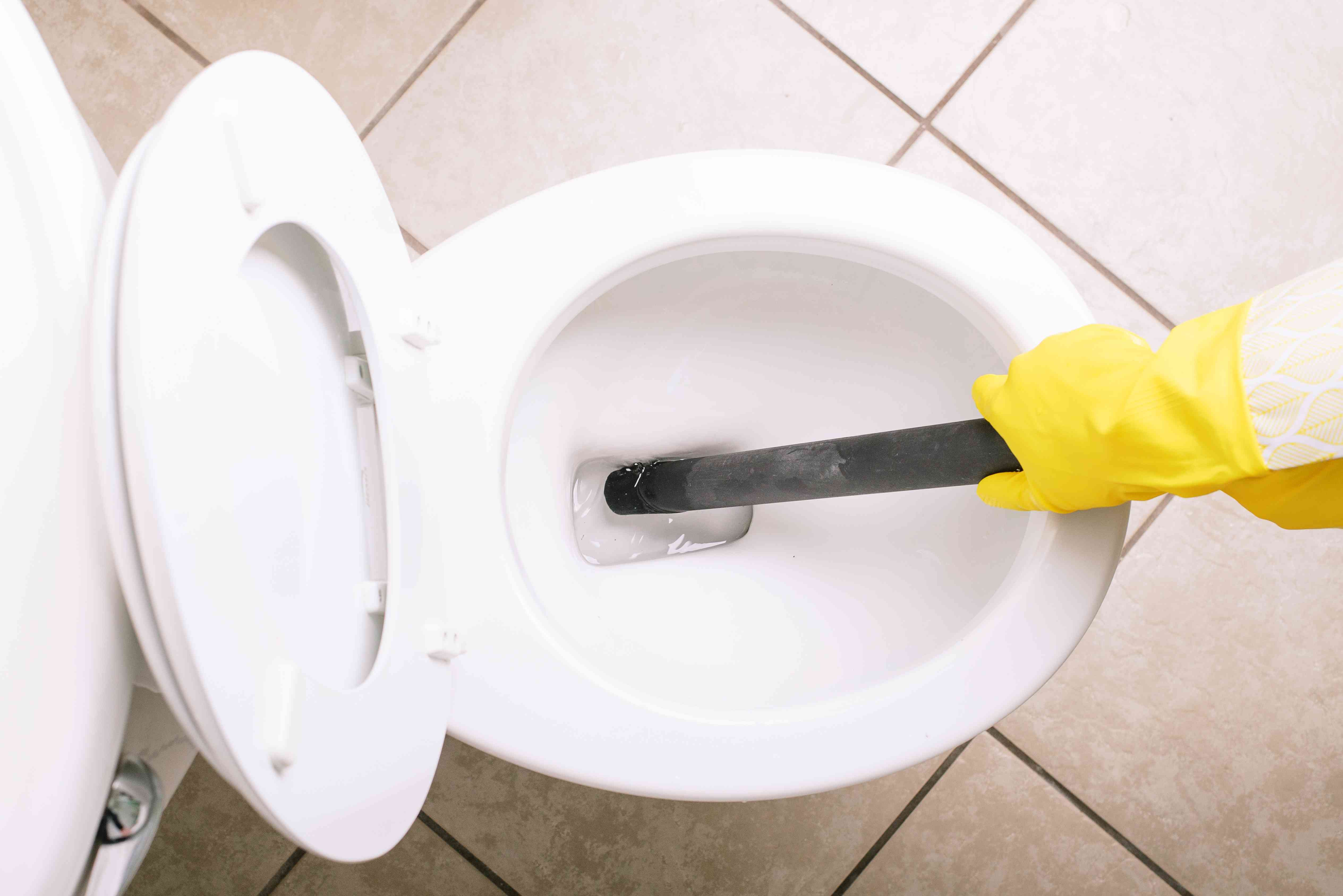 Wet-dry vacuum hose sucking up water to drain white ceramic toilet with yellow gloves