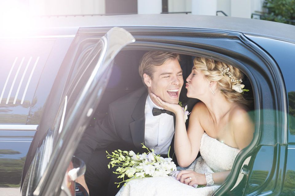 A bride and groom kissing in a limo