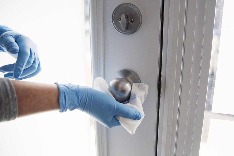Woman with gloved hands wiping doorknob