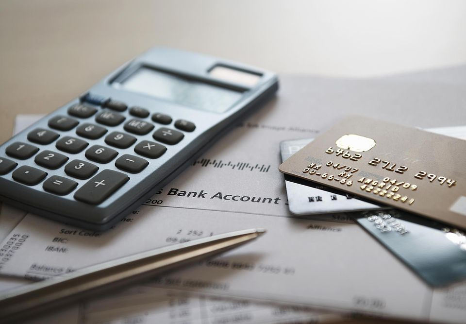 Calculator, pen and credit cards on bank statements