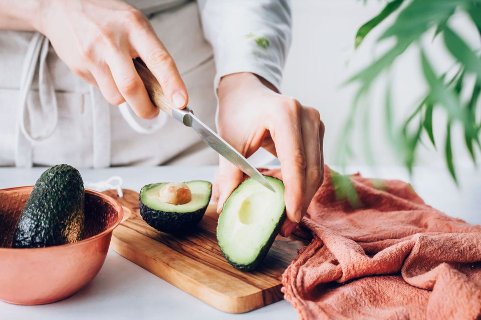 a woman slicing an avocado