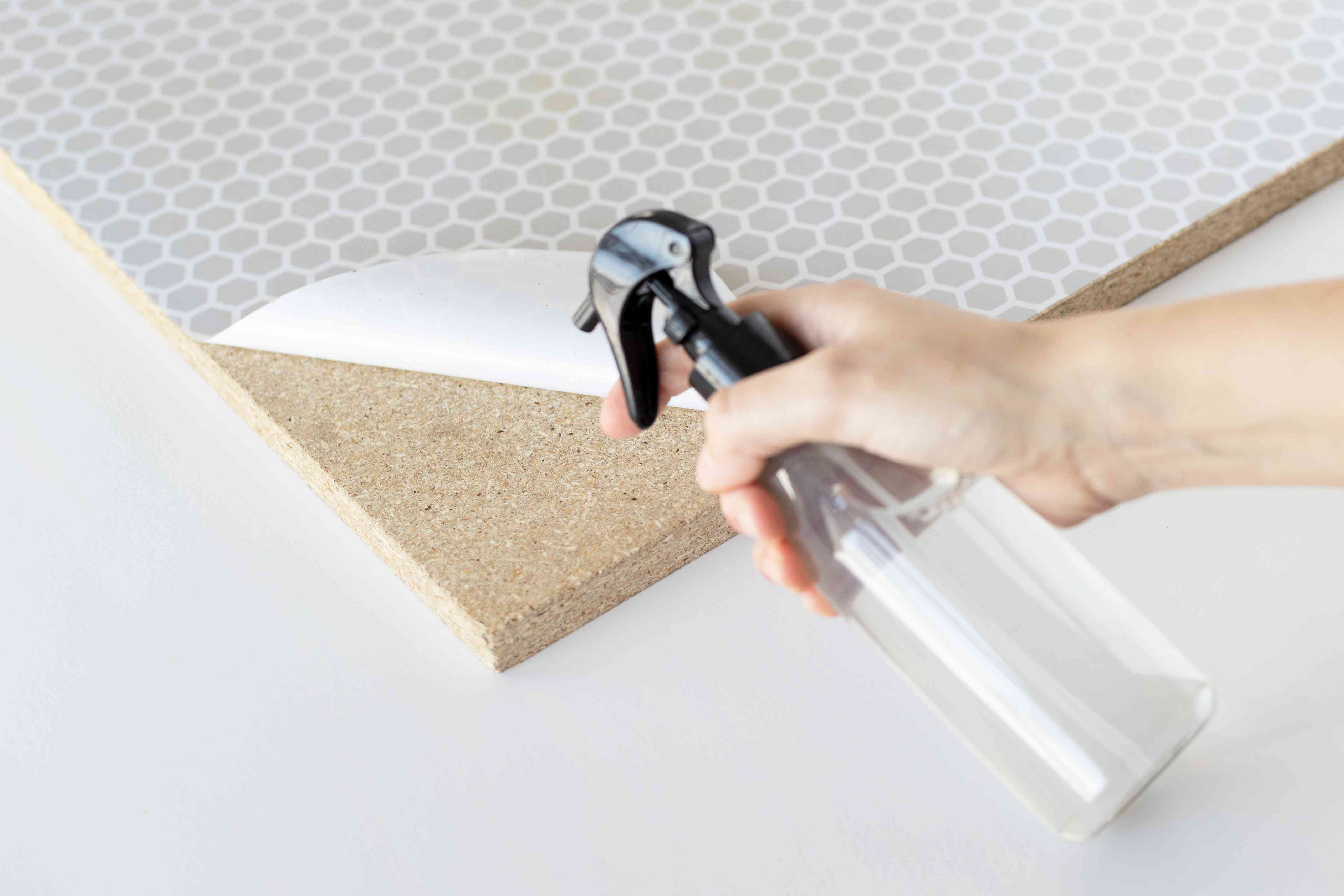 spraying the adhesive side of the shelf liner