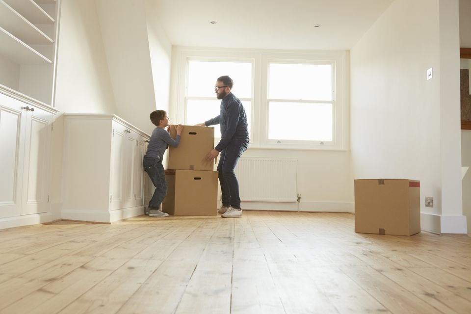 A father and son moving boxes out of a room