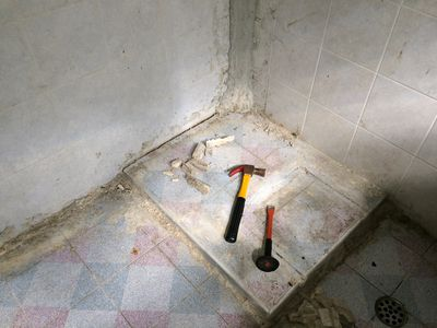in progress demo of a bathroom with tools on the tile floor