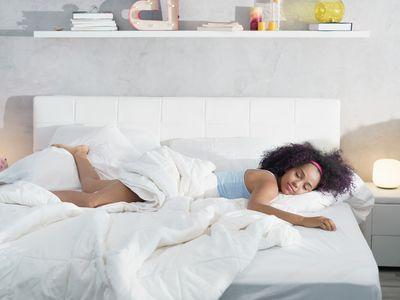 Happy woman sleeping on a large mattress