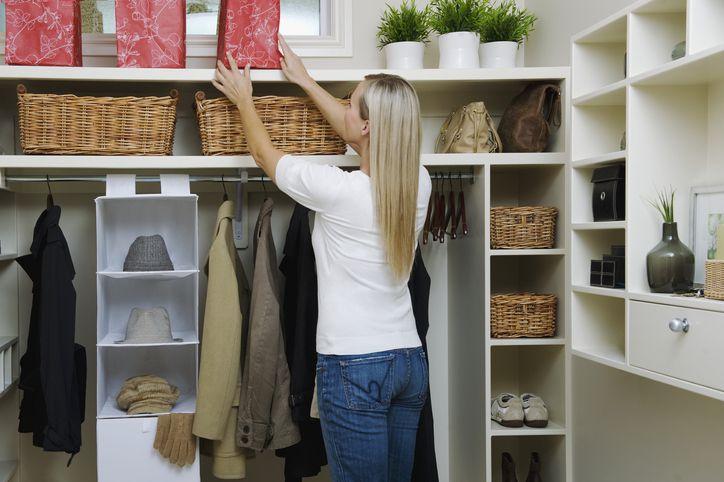 Woman reaching in shelf in well-organized closet
