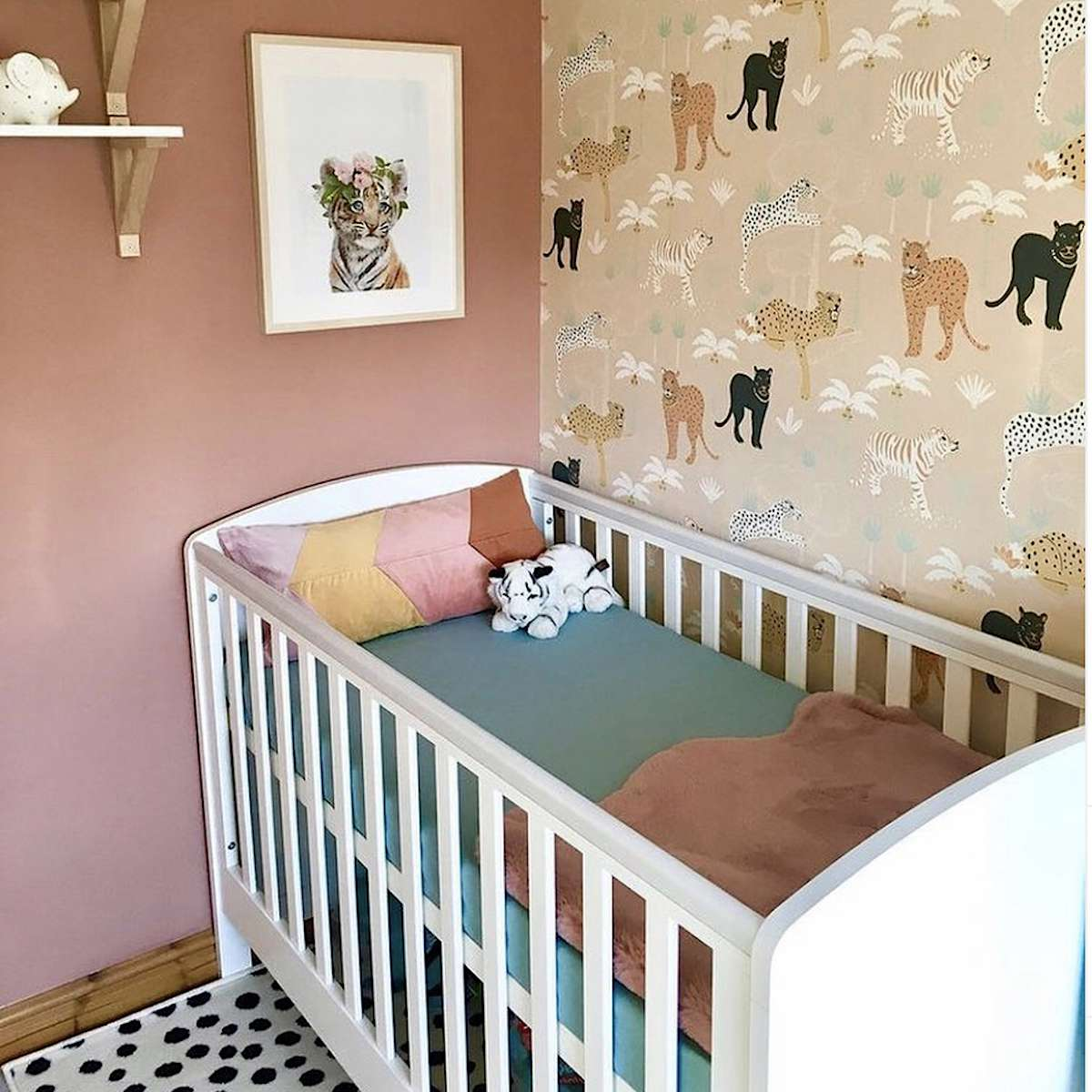 jungle theme nursery with peach wall and white crib