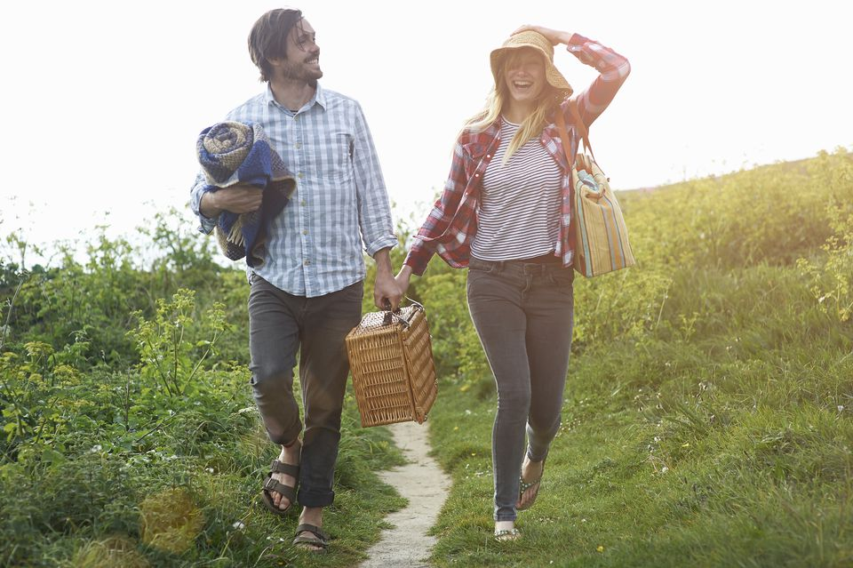 Couple walking and laughing on coastal path with picnic hamper