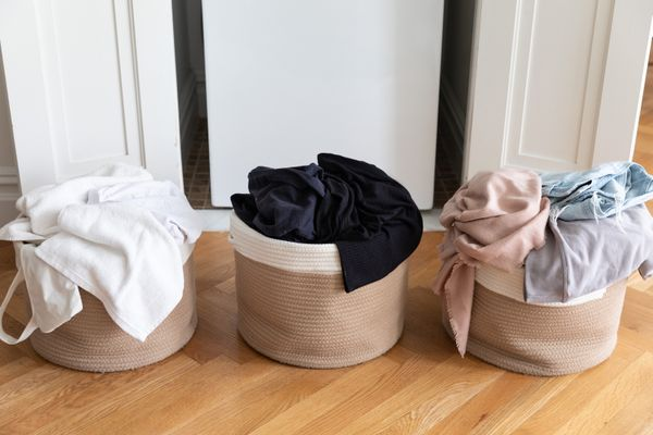 Laundry separated into different baskets by color before cleaning