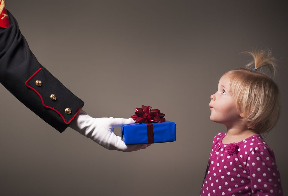 A child being given a present by a uniformed hand
