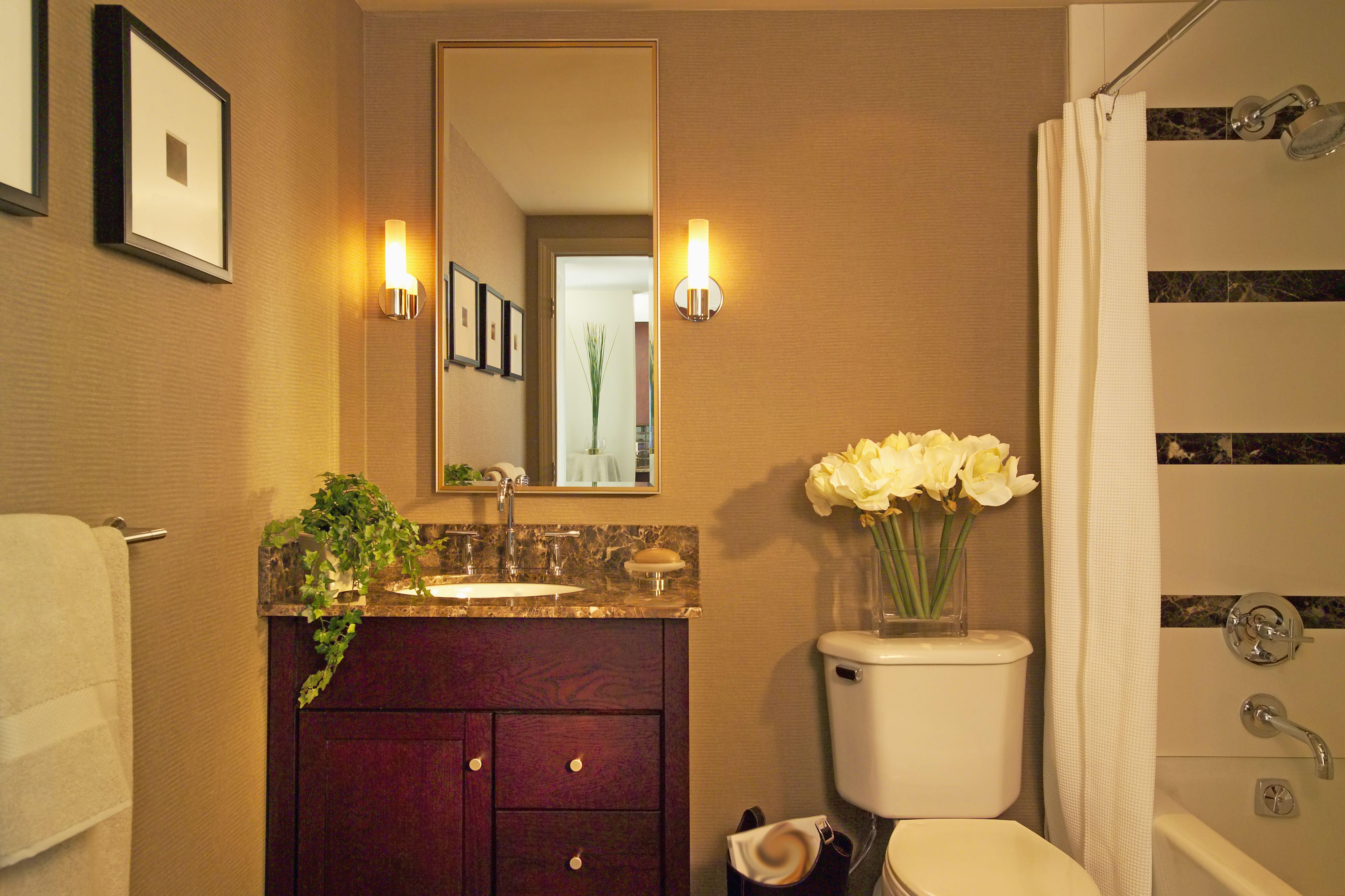 Mueble de madera y espejo con apliques de pared en baño doméstico