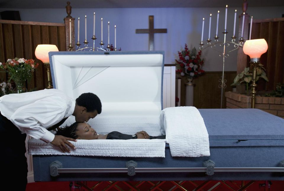 Young man kissing teenage girl lying in coffin