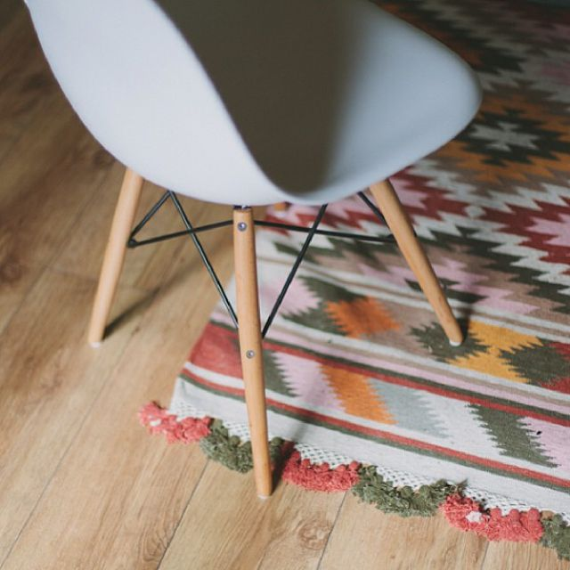Patterned area rug and midcentury shell chair