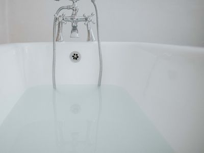 half-filled tub with view of faucet and overflow gasket