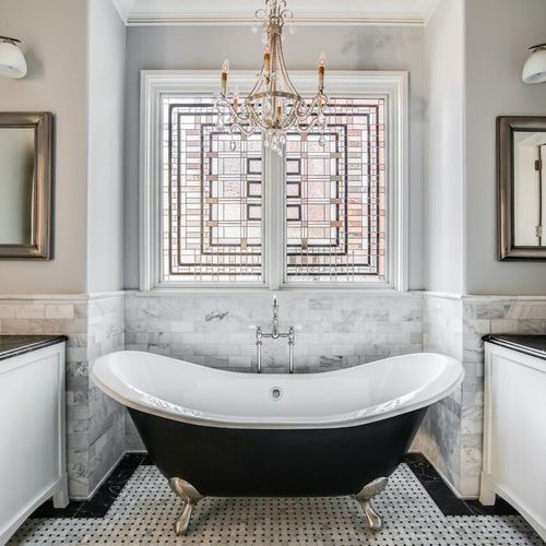 Luxurious black and white bathroom with stained glass window
