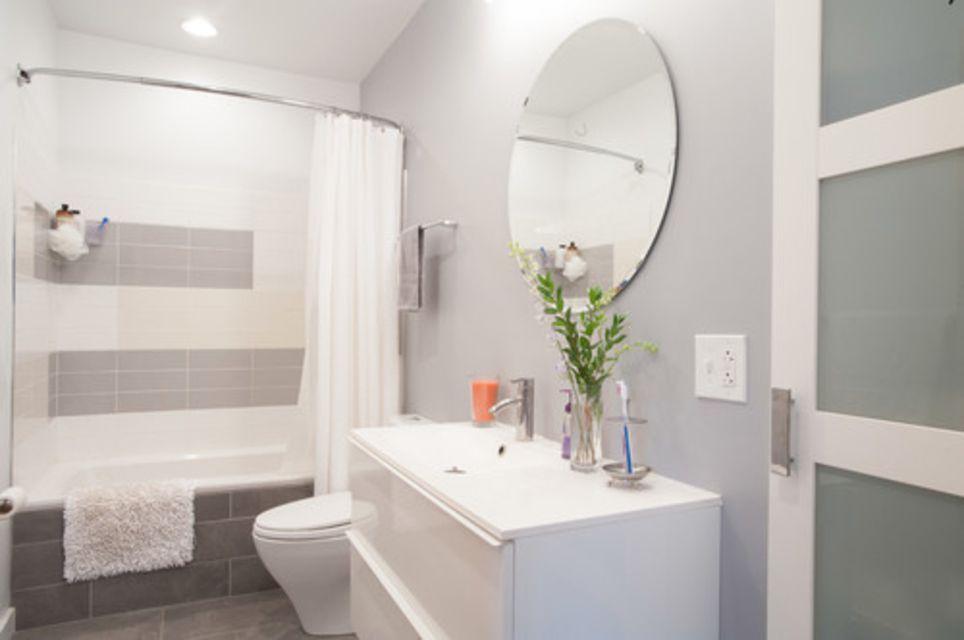 Grey and white bathroom with circular mirror and tiled bathtub.