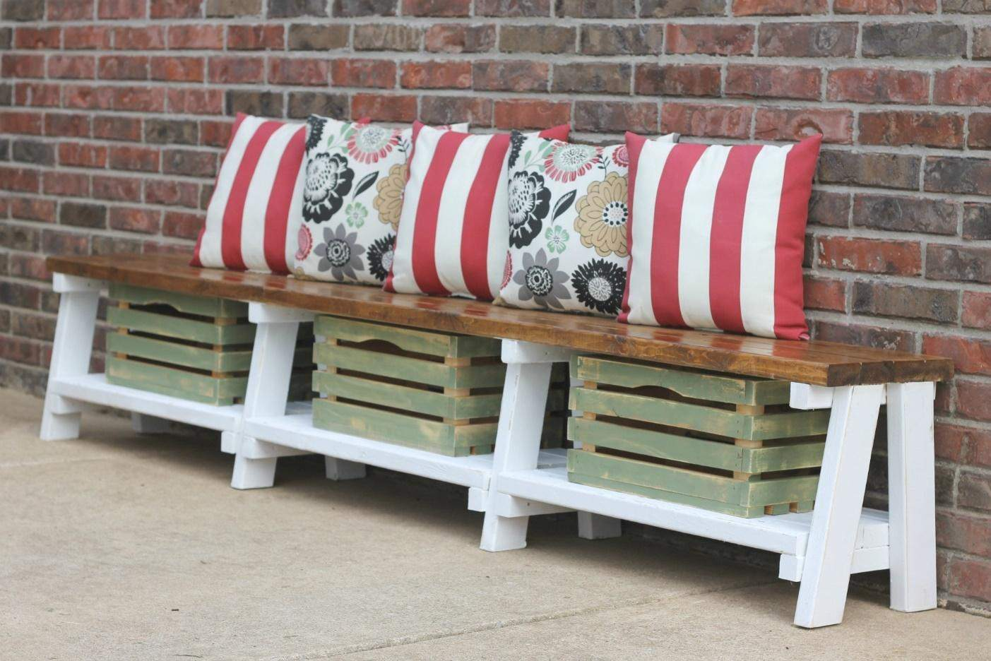 Crates placed beneath a bench with pillows on top