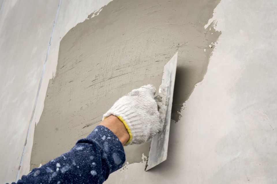 Close-up of plastering wet cement on the wall