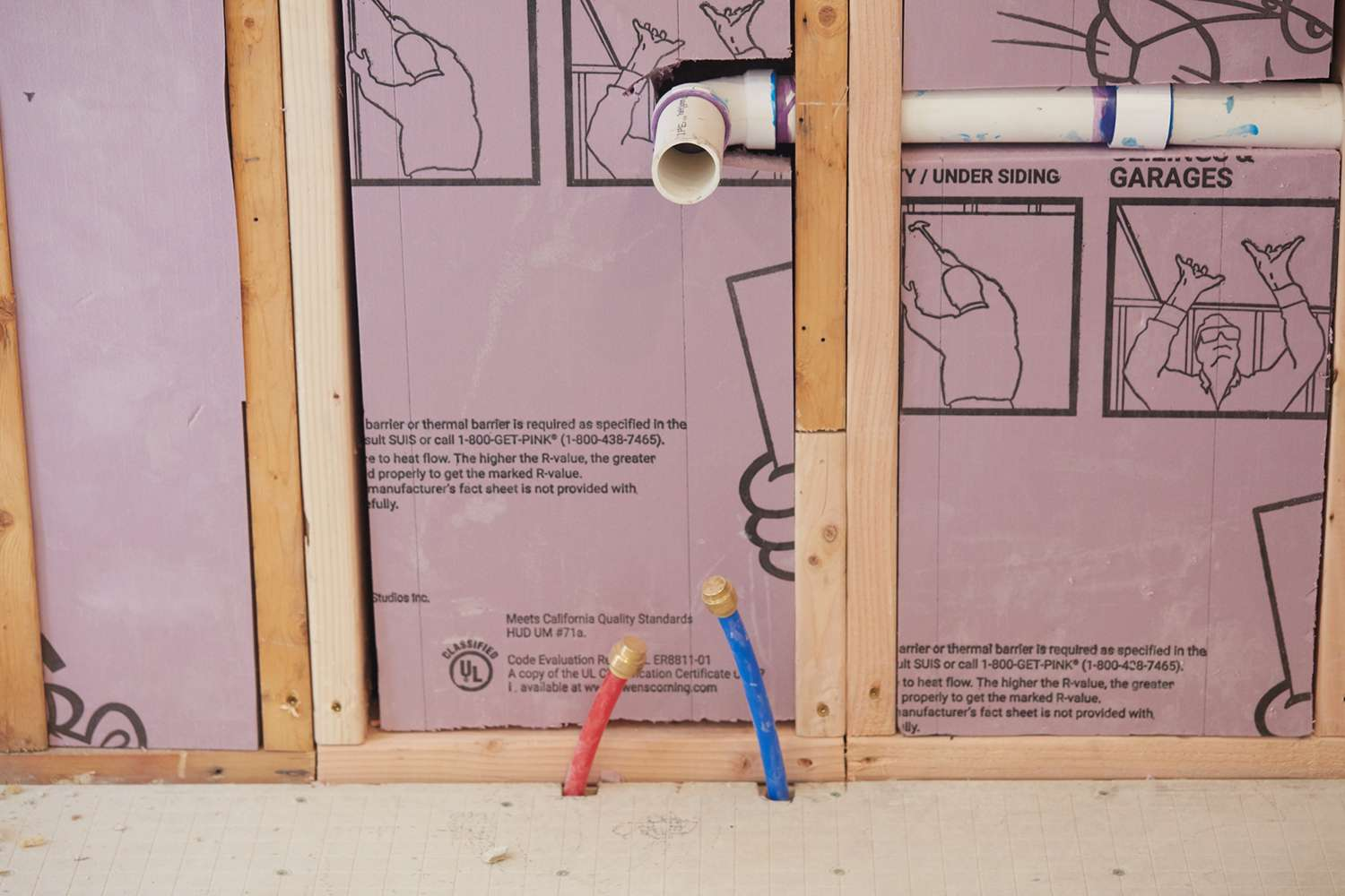 Plumbing tubes and pipes in front of exposed dry wall with insulation