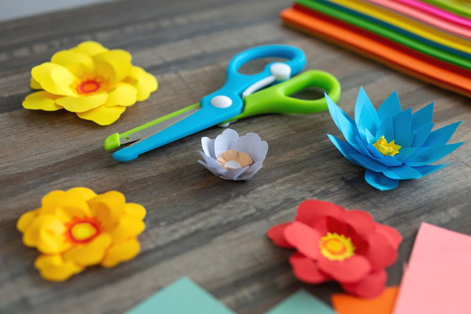 Close up of colorful color paper flowers and scissors on wooden desk. Art studio workplace concept