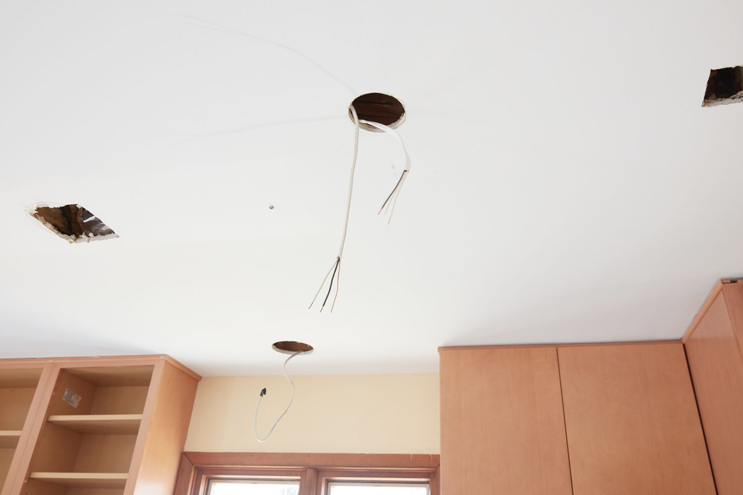 Recessed lighting holes in ceilings with wire dangling needing patches